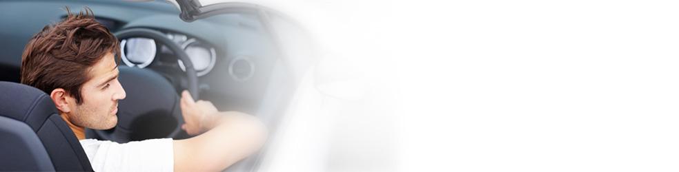 Junger Mann mit braunem Haar sitzt in einem weißen Cabrio mit dem Rücken zum Betrachter, die Hände am Lenkrad.